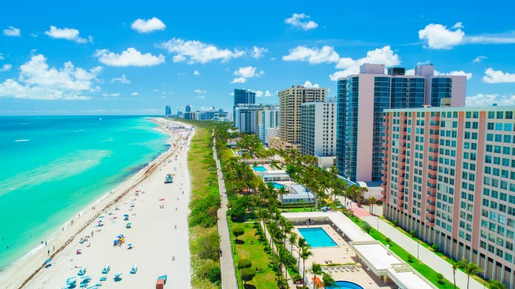 Photo is an aerial view of South Beach located in Miami that features large condo buildings, white sand, and blue ocean water.