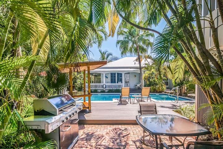 Airbnb in Key West bbq, pool and benches on shaded patio, surrounded by palm trees.