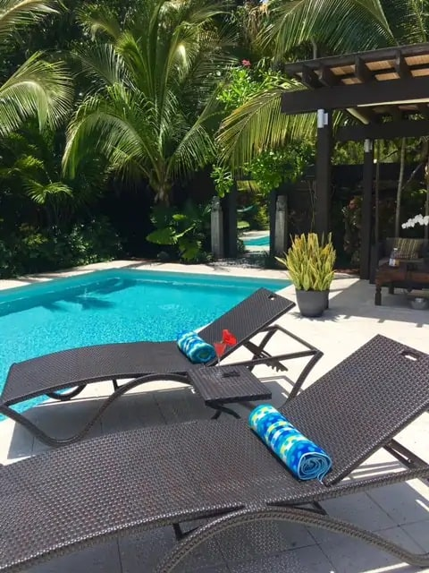 Photo of stunning pool with lounge chairs and lush garden at an Airbnb in Miami.