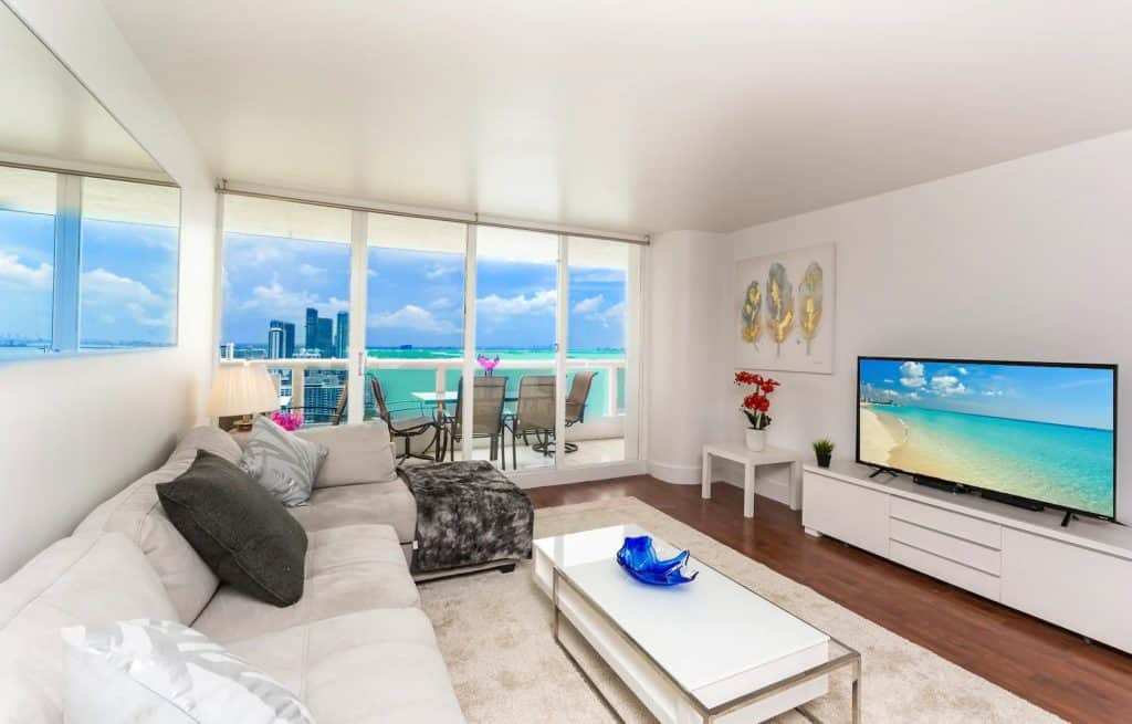 Photo of ocean view balcony and living room inside a condominium Airbnb in Miami.