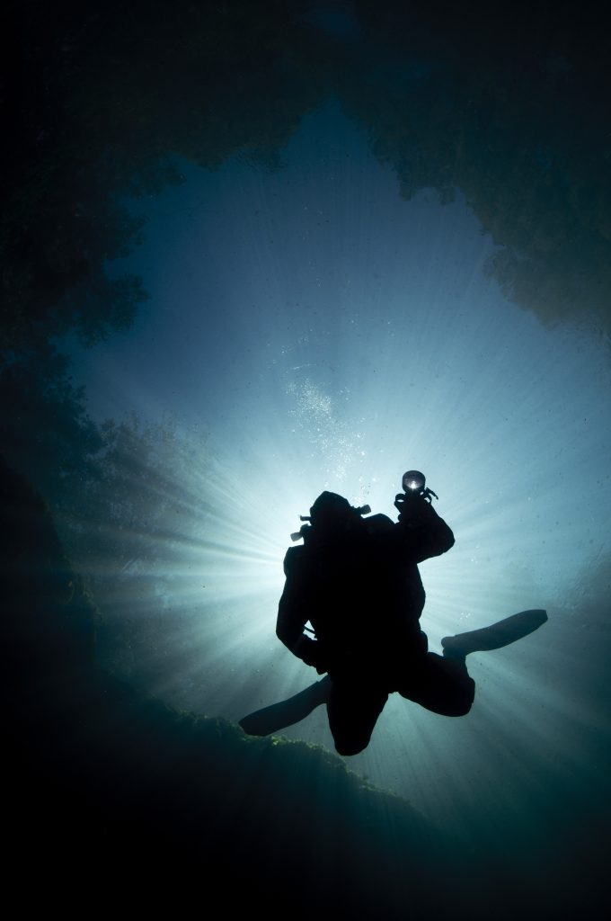 silhouette of diver in underwater cave