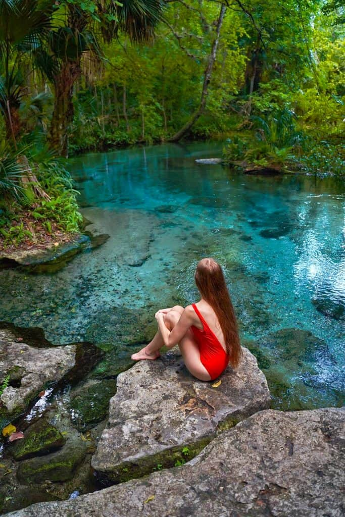 woman sitting on rock by blue spring water surrounded by greenery day trips from Orlando
