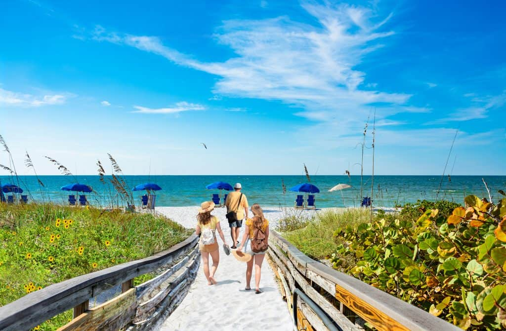 people walking along sandy path to beach with blue umbrellas day trips from Tampa