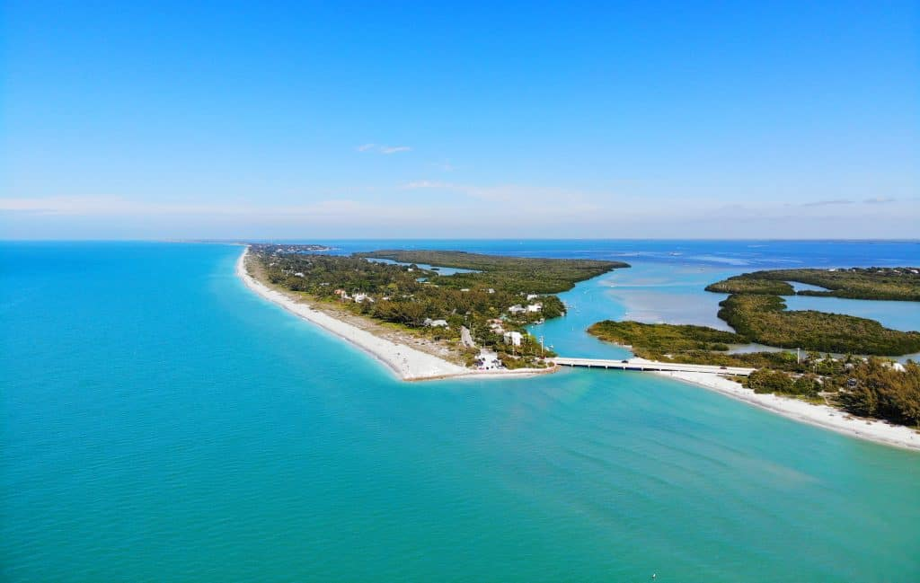 aerial shot of greenery-filled island surrounded by light blue water day trips from Tampa