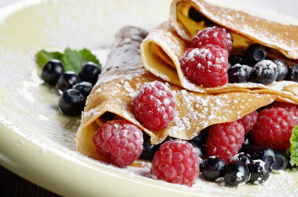 Delicious sweet crêpes with fresh raspberries and blueberries covered with powdered sugar