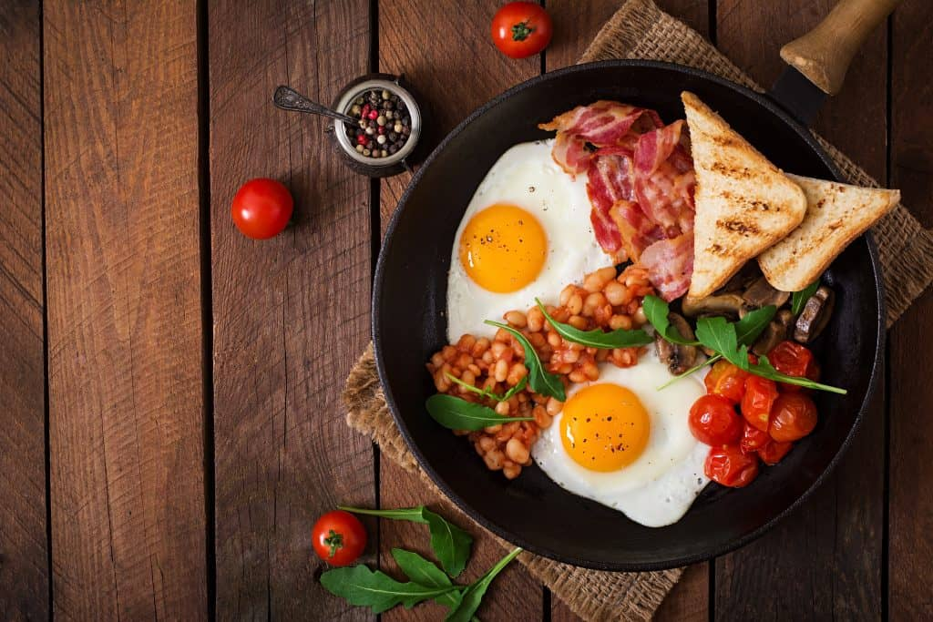 Over easy eggs, with bacon and toast with roasted tomatoes and baked beans, set served in a skillet.