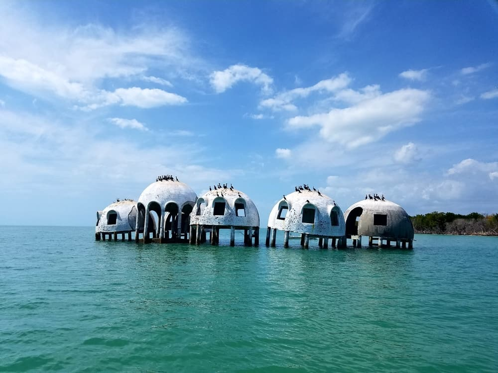 The dome houses are abandoned and on stilts, surrounded by water.
