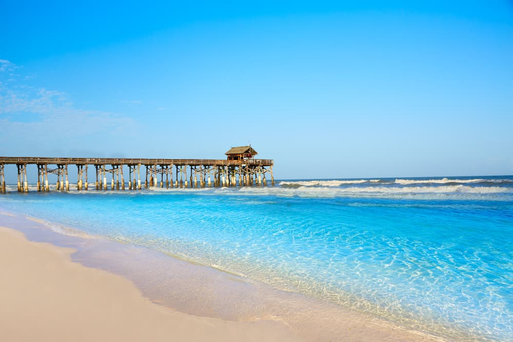 bright blue waters  of beach with brown pier in the distance weekend getaways in Florida