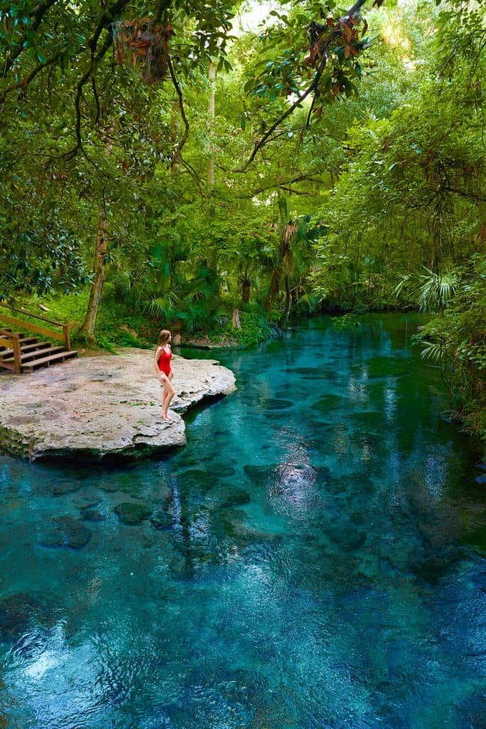 woman standing on edge of bright blue spring surrounded by greenery weekend getaways in Florida