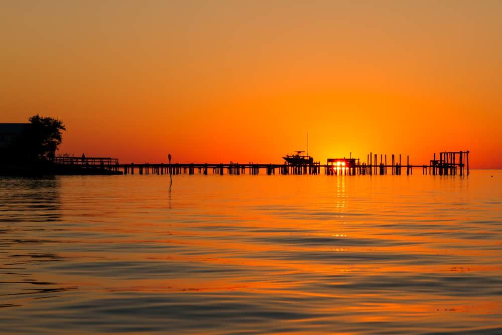 bright orange sunrise behind pier