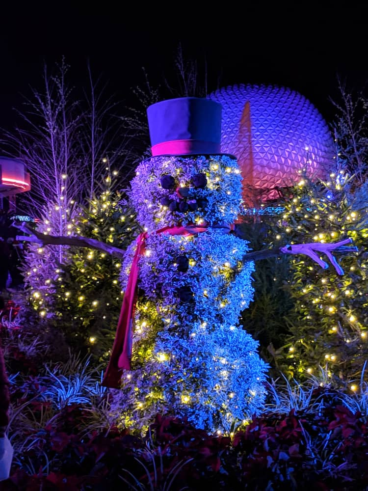 A smiling snowman lights up and greets guests at Disney World during Christmas in Orlando.