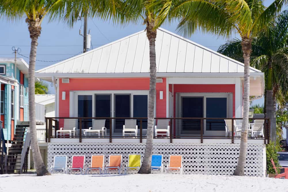 This bright-colored home is one of the many cottages in Florida that sits beachfront with an inviting outdoor space.