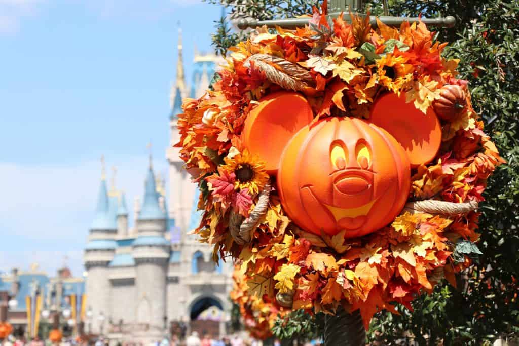 A smiling pumpkin Mickey Mouse laid in an autumn wreath greets guests on their way to Cinderella's Castle at Mickey's Not-So-Scary Halloween Party, the ultimate way to celebrate Halloween in Florida.