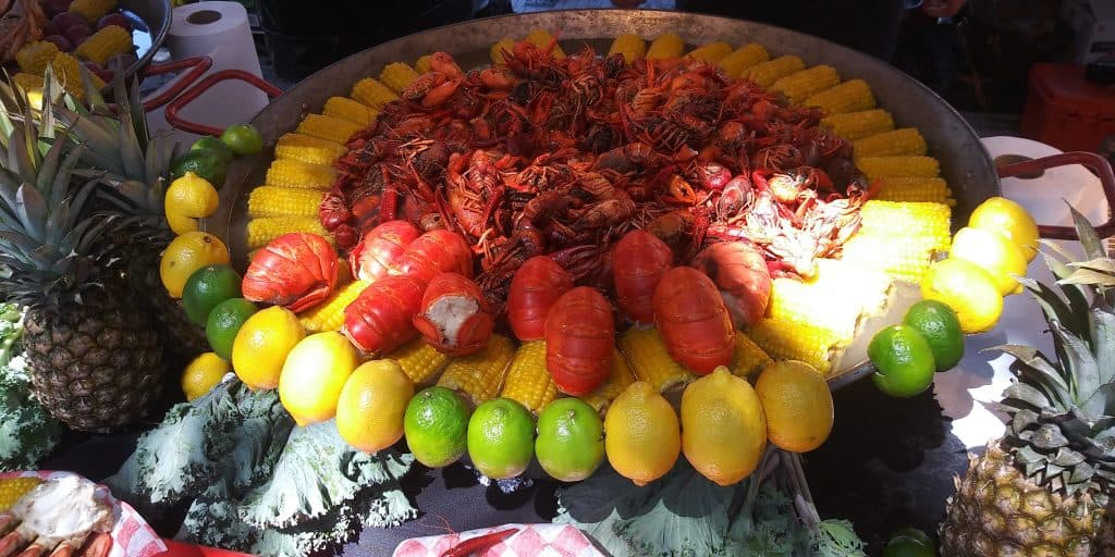A gigantic platter of seafood and shellfish surrounded by corn on the cob awaits the visitors of the Pensacola Seafood Festival, a perfect way to enjoy Florida in fall.