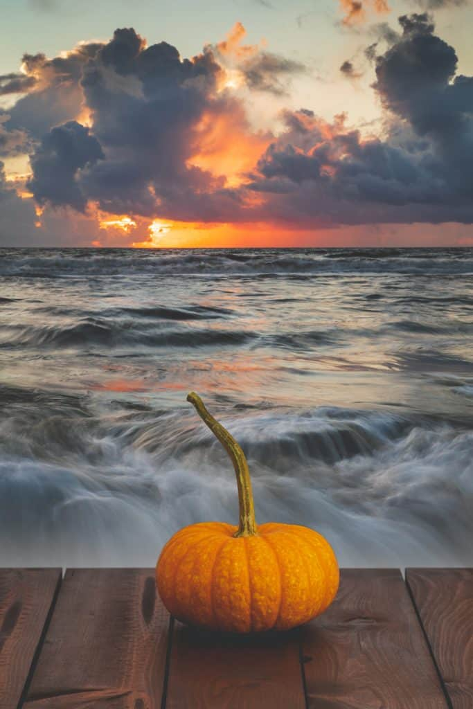 A pumpkin sits on a dock as waves crash, ringing in the beginning of fall in Florida.