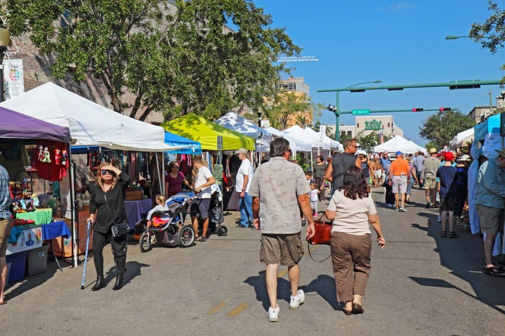 Pedestrians walk through the streets of downtown at the Sarasota Farmers Market, a highlight of Florida in fall.