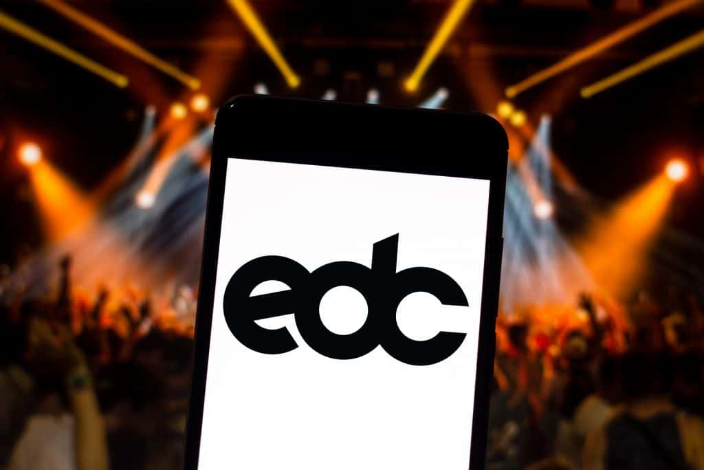The logo of the Electric Daisy Carnival displayed on a cell phone, floating over a sea of concert-goers at one of the biggest and brightest fairs in Florida.