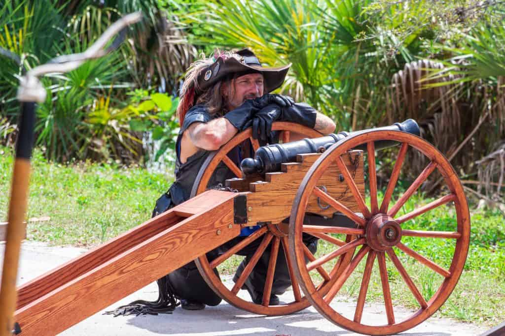 A swashbuckler perches on his cannon at the Florida Renaissance Festival.