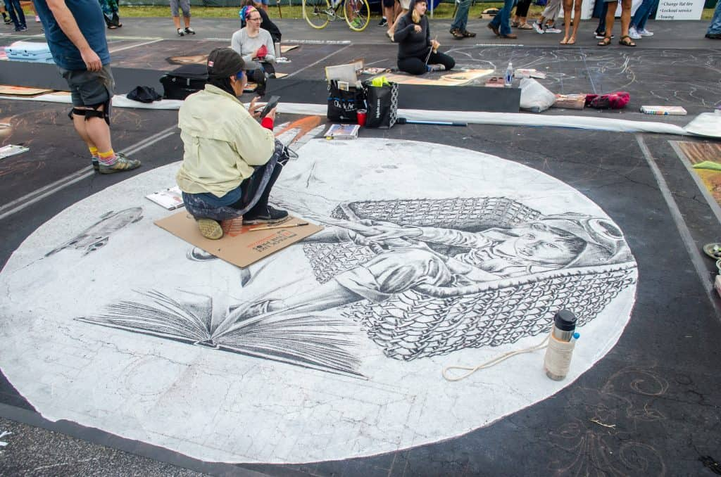 An artists works on a massive chalk masterpiece of a boy in a basket at the International Chalk Festival in Venice Beach, Florida.
