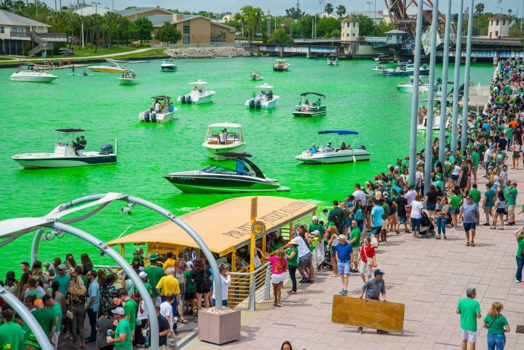 Boats sail along the Hillsborough River, dyed green for the River O'Green Festival in Tampa, Florida.
