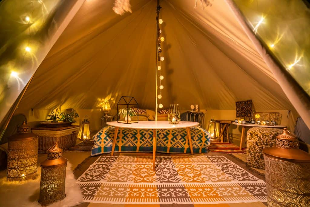 The cozy, warm interior of a bohemian-decorated glamping tent.