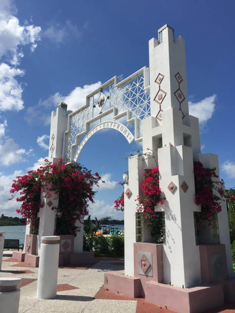 The stone arch entrance to Bayfront Park, with bougainvillea flowers pouring out, one of the best things to do in Sarasota.
