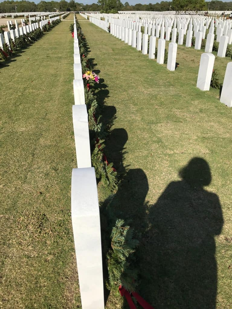 The shadows of mourners look on the lines of headstones in the Sarasota National Cemetery, adorned with wreaths.