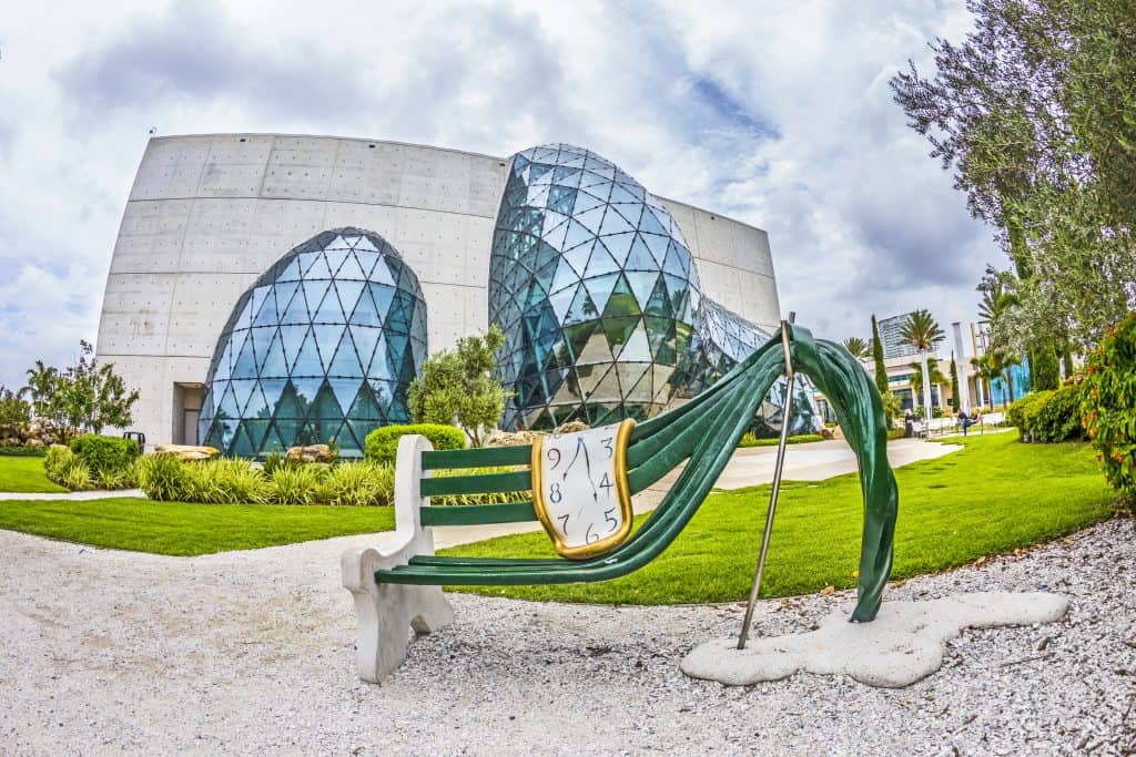 Glass sculpture in front of the Dali museum as a fun thing to do in St. Petersburg Florida with a Salvador Dali work of art as a museum bench