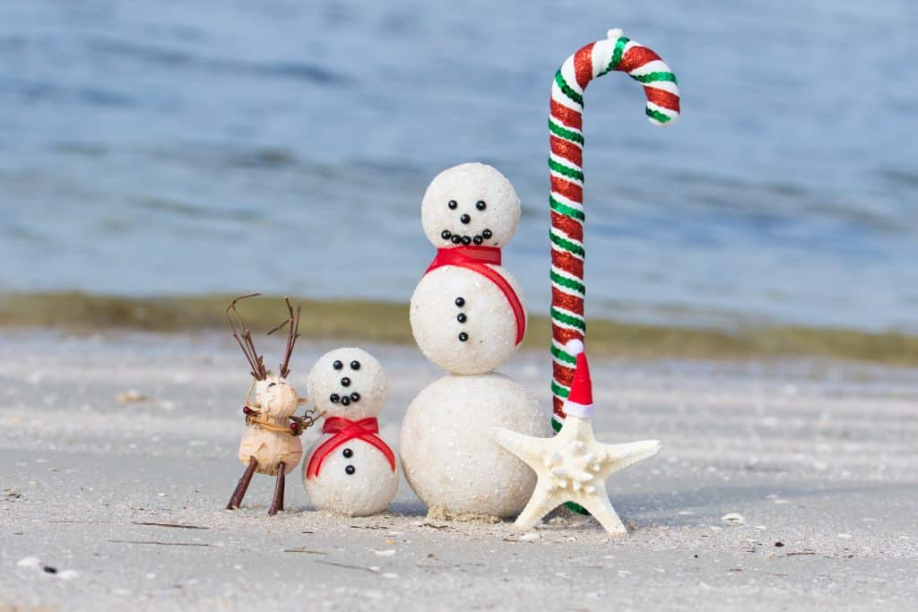 Snowmen made of sand celebrate winter in Florida on a beach!