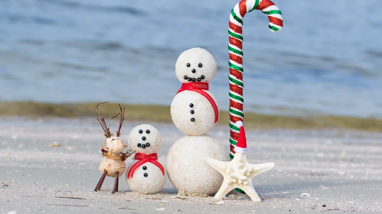 Snowmen made of sand sit on a beach in Florida in winter.