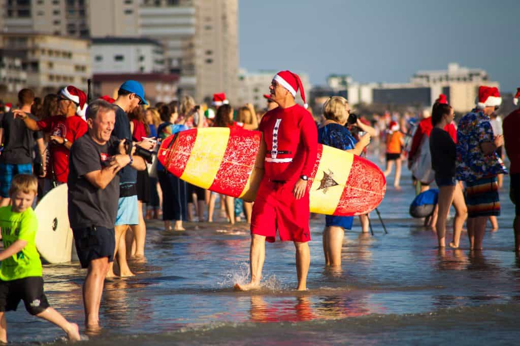 A surfer dressed as Santa walks along Cocoa Beach during Surfing Santas