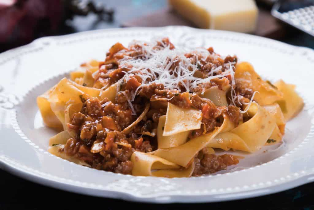 Photo of a white plate serving pasta with a Bolognese sauce.