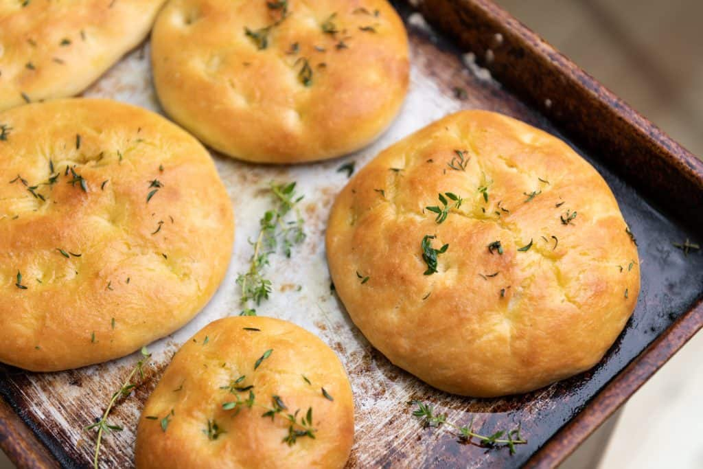 Photo of focaccia bread on a baking pan.