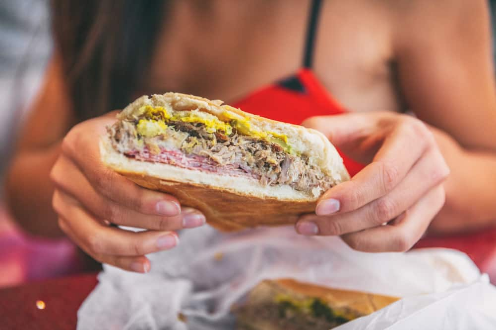 woman holding Cuban sandwich