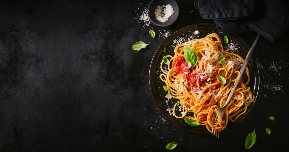bowl of pasta garnished with basil leaves