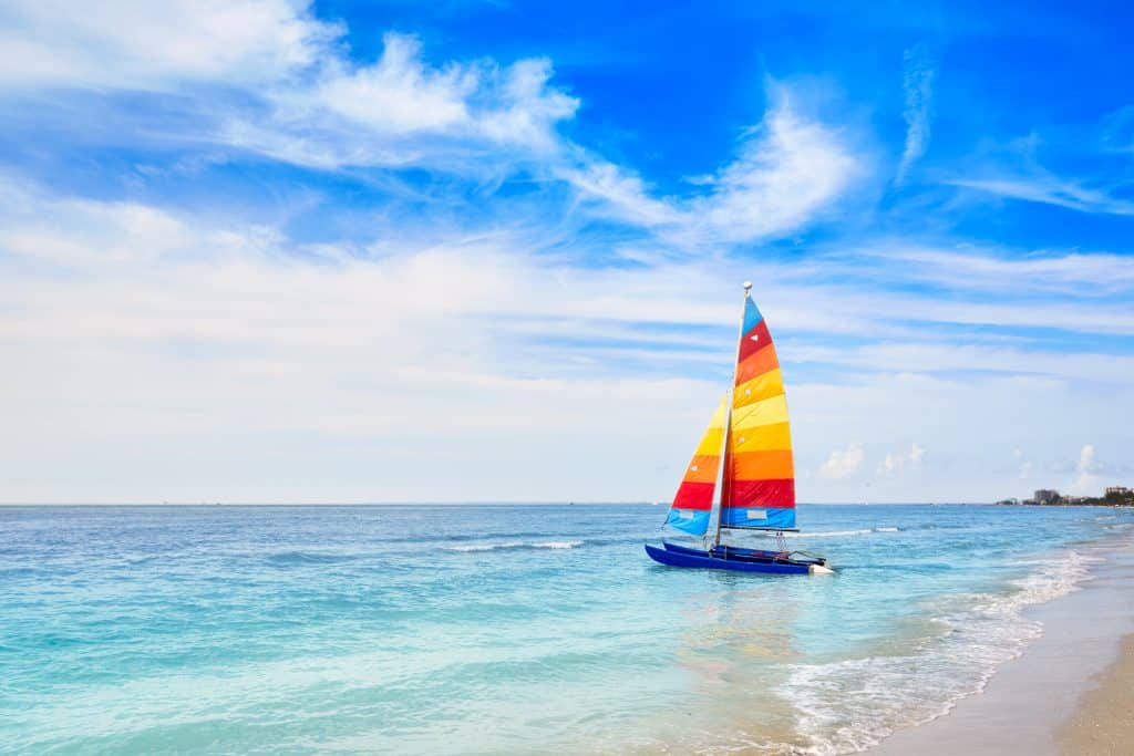 A sailboat glides along the gorgeous, turquoise waters of the best beaches in Naples.