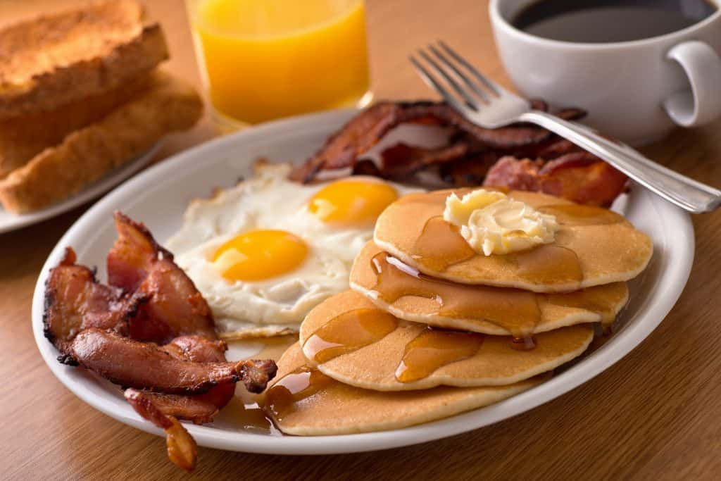 A breakfast platter holds bacon, eggs, and pancakes.