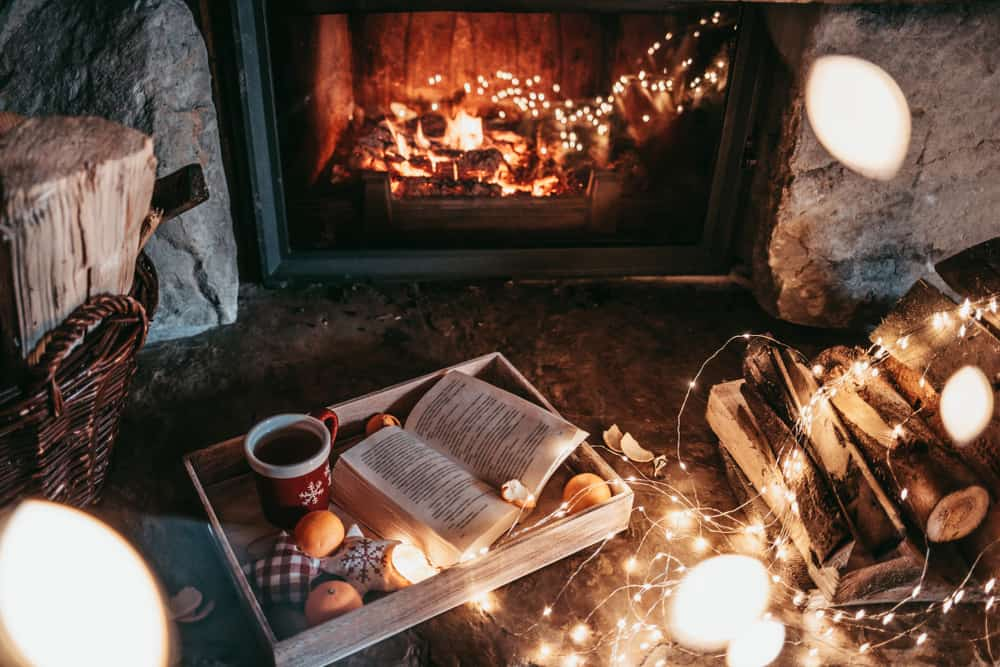 Photo of cozy inside of a cabin with lights and a fireplace.