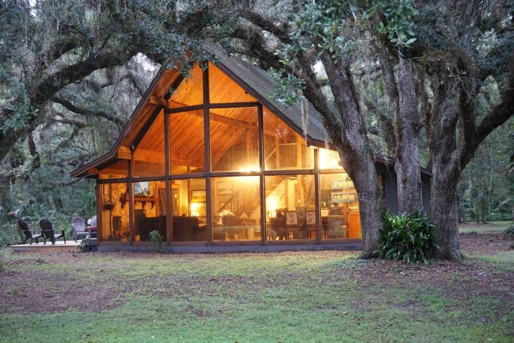 Photo of The Nature House, one of the best cabins in Florida, under two large trees.