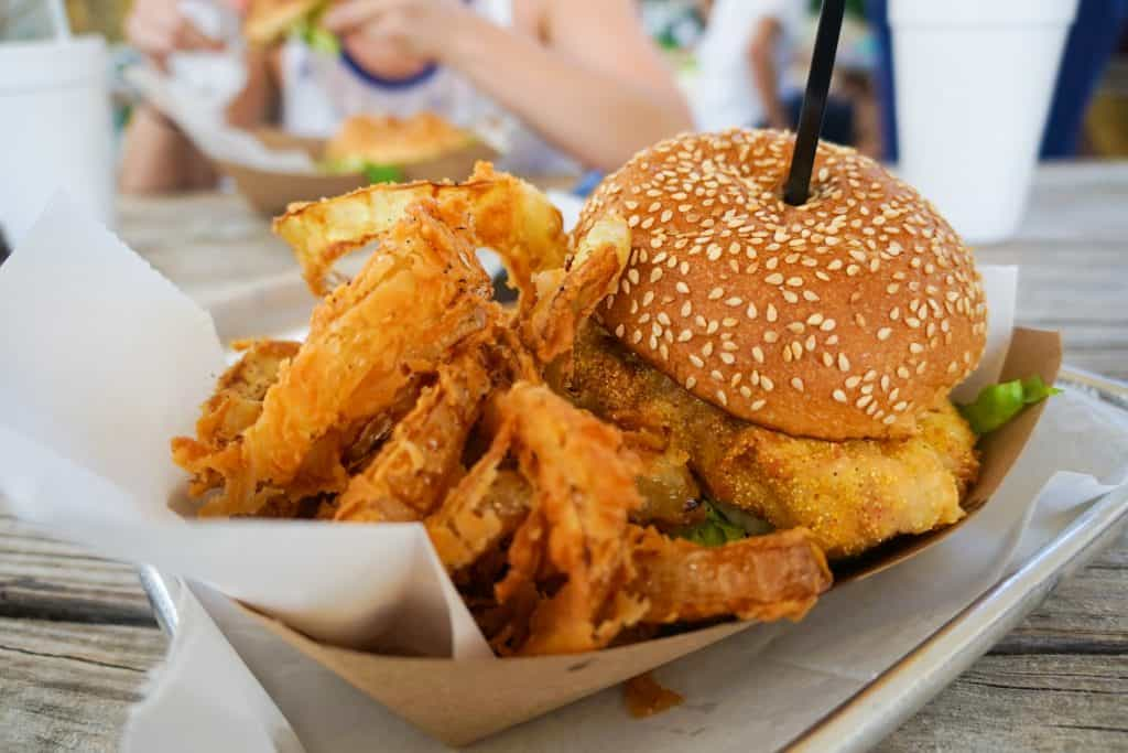 The infamous Grouper Burger at Big Ray's Fish Camp with hand-battered onion rings, one of the best restaurants in Tampa.