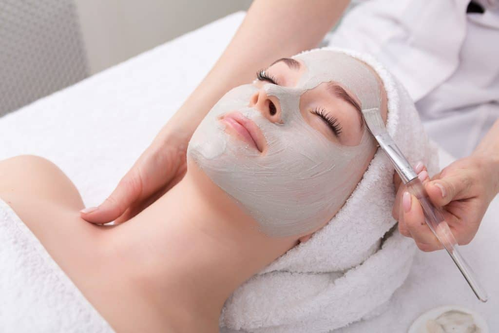 A mask treatment is applied with an exfoliating brush in one of the best spas in Florida.
