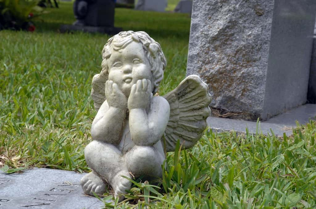 A cherub angel sits on a grave at the Greenwood Cemetery in Orlando, Florida.