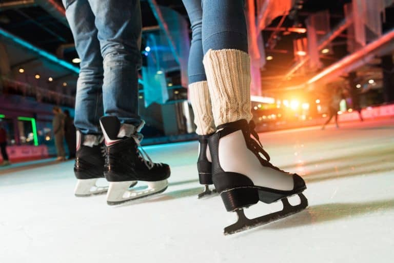 A couple ice skates in an indoor ice rink.