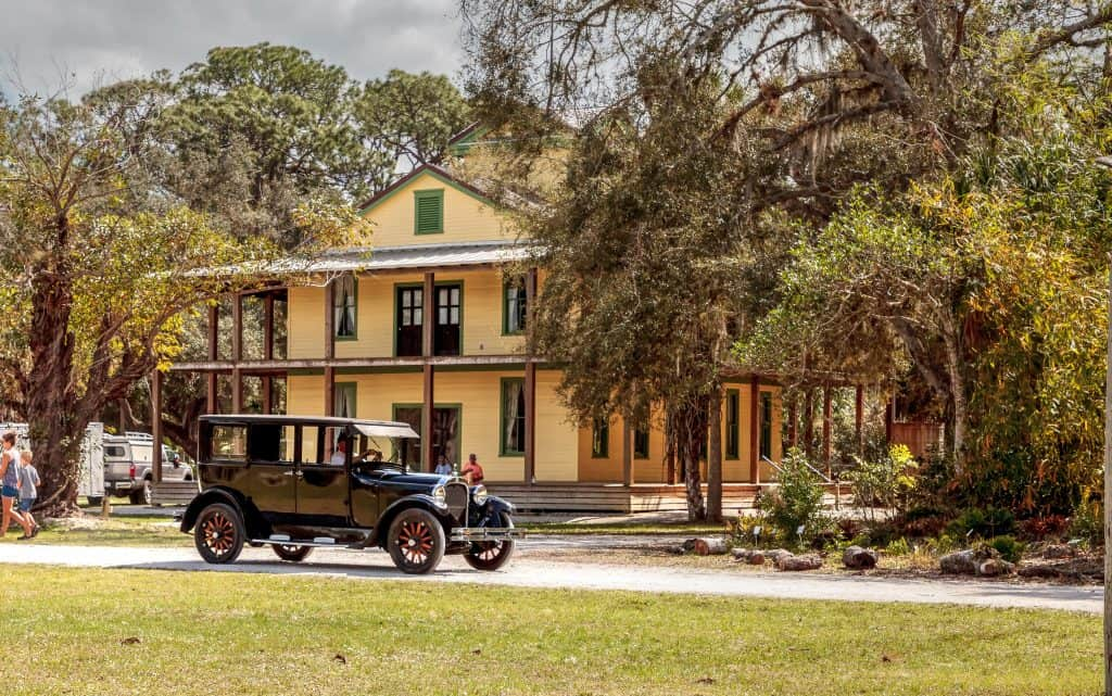 A vintage car sits outside a preserved building on the grounds of Koreshan State Park.