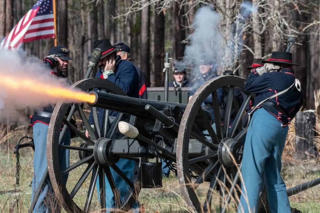 At a reenactment, soldiers fire a cannon at their enemies at Olustee Battlefield Historic State Park.