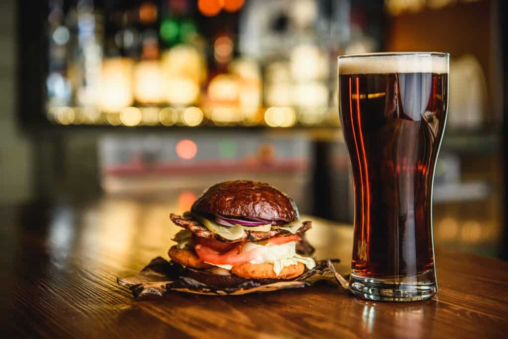 Photo of a dark beer and sandwich in a pub setting.