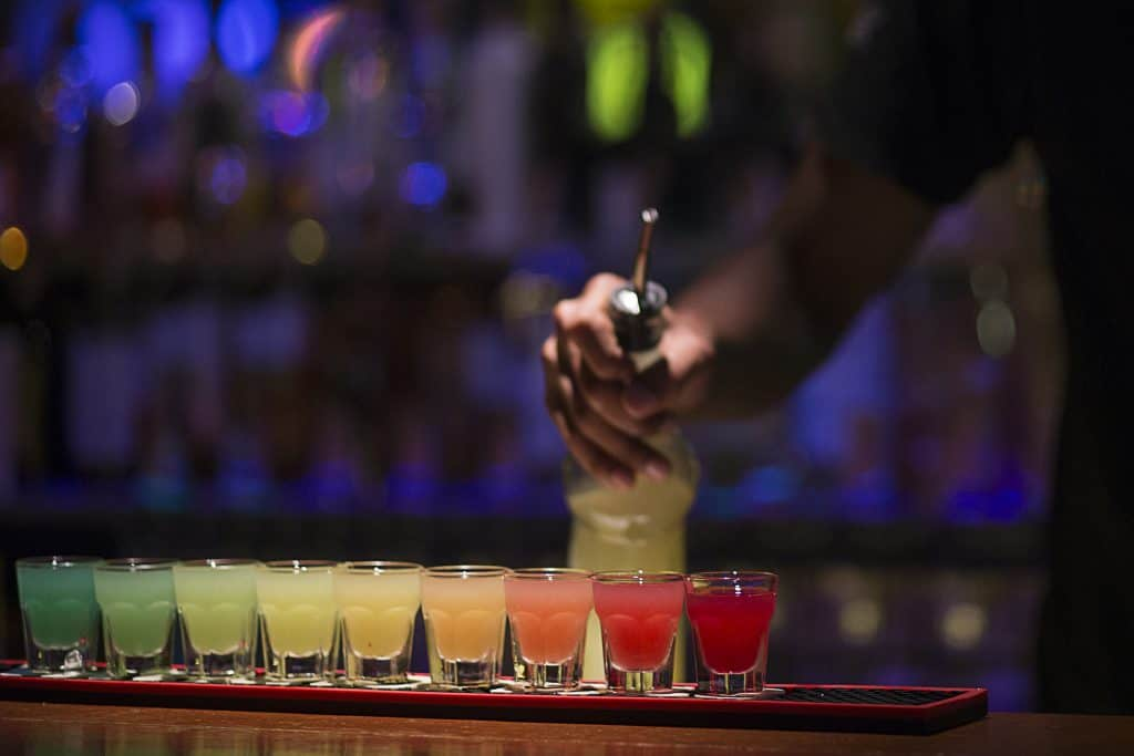 Photo of rainbow colored shots lined up on a bar top.