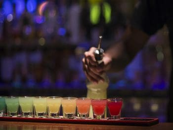 Photo of rainbow colored shots lined up on a bar top