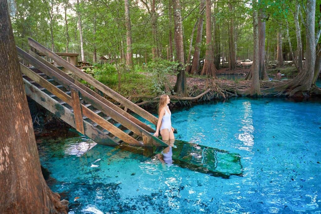 woman walking down stairs into Ginnie Springs | pretty blue water at Ginnie Springs | best springs in Florida