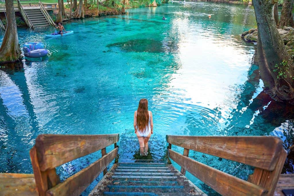 standing at the bottom of an entrance into Ginnie Springs with crystal clear blue water in Florida